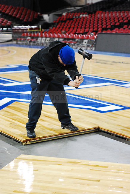 Kentucky Exposition Center staff  member tightens the basketball court planks with a rubber mallet at Freedom Hall on Monday December 5, 2010. Photo by Ryan Buckler | Staff