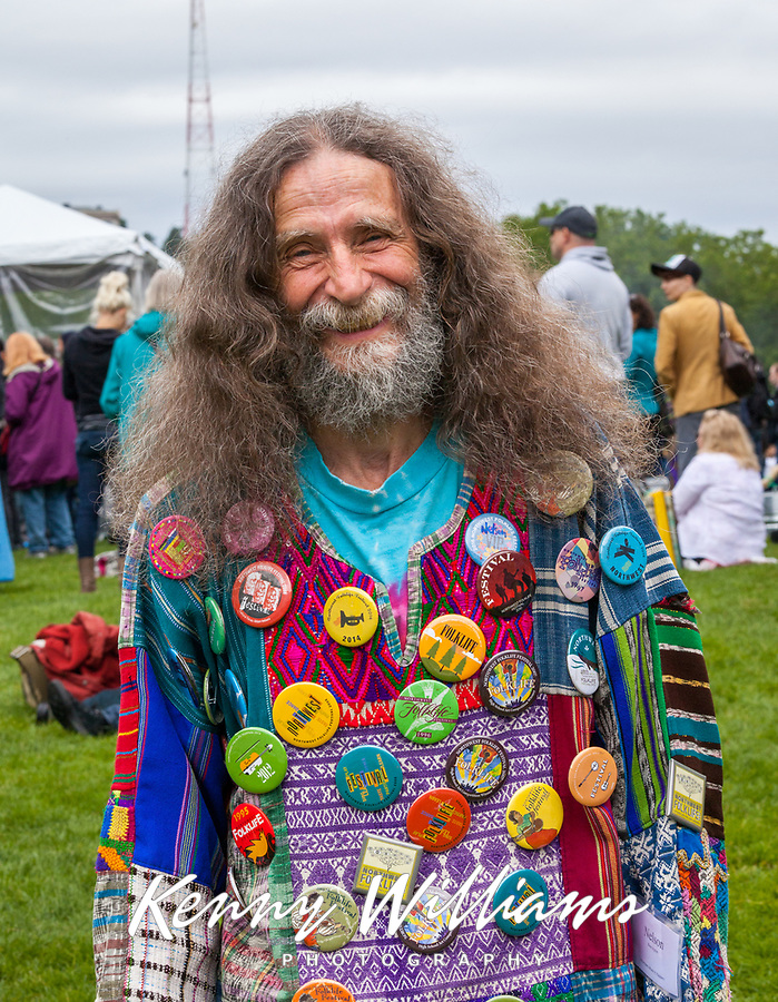 Colorful old bearded hippie man wearing shirt covers with button from Northwest Folklife Festival, Seattle Center, Washington, USA.