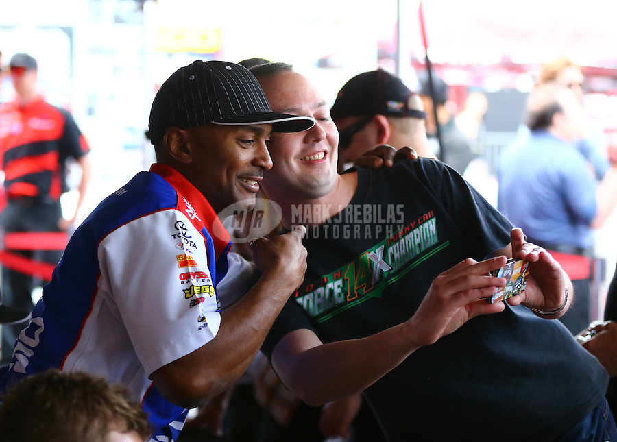 May 31, 2014; Englishtown, NJ, USA; NHRA top fuel driver Antron Brown poses for a selfie with a fan during qualifying for the Summernationals at Raceway Park. Mandatory Credit: Mark J. Rebilas-