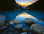Banff National Park, Alberta, Canada    <br /> Sunrise lights Mount Victoria and Victoria Glacier with reflections on Lake Louise and shoreline boulders