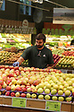 Greengrocer in the produce department arranging apples