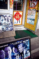 Movie posters advertise DVD's for sale at a small shop in Harbin, Heilongjiang Province, China.
