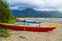 Outrigger canoes and distant beachgoers at Kaua'i's Hanalei Beach at sunset.