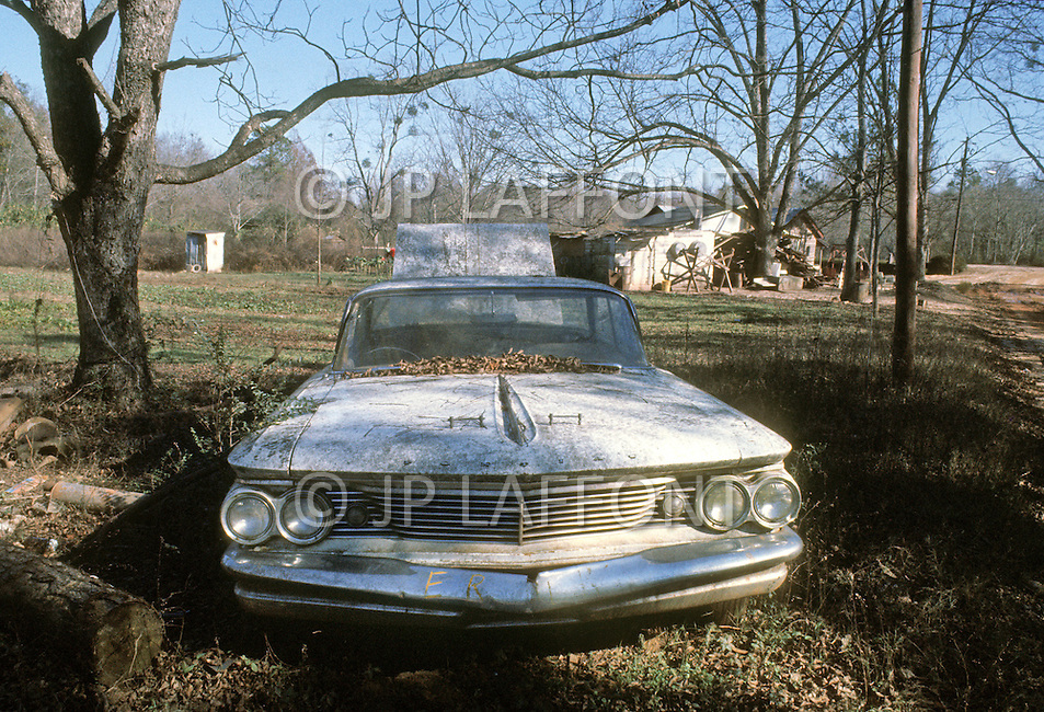 December 1976. Americus, Georgia. Poor housing with abandoned car near Americus.