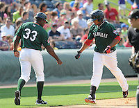 Left fielder Keury De la Cruz (25) of the Greenville Drive, right, is congratulated by manager Carlos Febles (33) after hitting a home run in a game against the Rome Braves on May 6, 2012, at Fluor Field at the West End in Greenville, South Carolina. Greenville won, 11-3. (Tom Priddy/Four Seam Images)