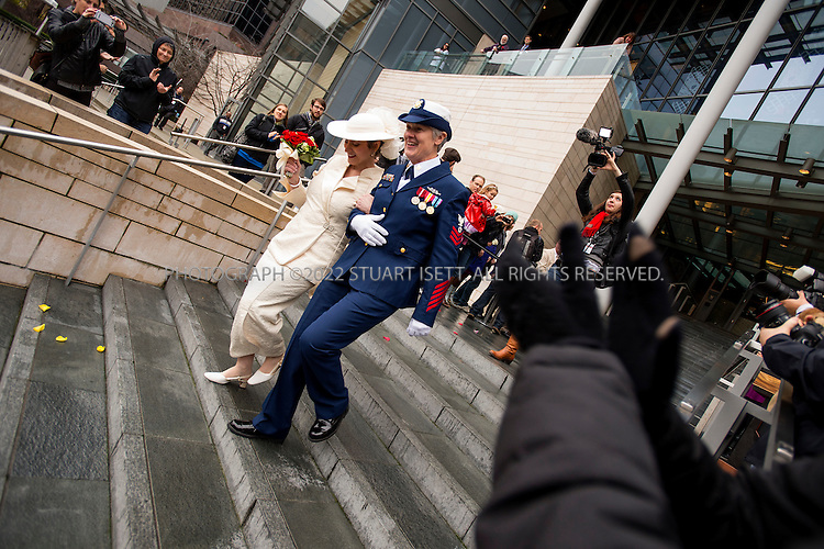12/9/2012--Seattle, WA, USA...Deb Needham, left, and Nancy Monahan, a retired member of the U.S. Coast Guard, walk down the stairs of Seattle City Hall after they were married..On the first day same sex couples were allowed to marry in Washington State, Hundreds of well-wishers braved cold and rain to celebrate 133 weddings at Seattle City Hall. Washington, Maine and Maryland last month became the first U.S. states to extend marriage rights to same-sex couples by a popular vote, in a leap forward for gay rights. A crowd of several hundred people waited outside City Hall in the cold to cheer couples as they descended the steps, some throwing bird seed, rice, blowing bubbles and handing flowers to the newlyweds...©Stuart Isett. All rights reserved.