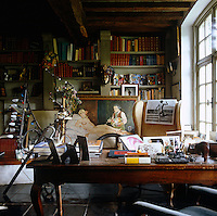 The study is cluttered with photographs and paintings on the desk and the shelves behind