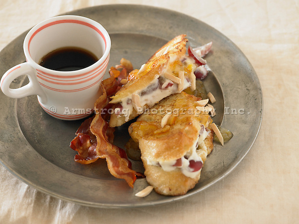 Almond and grape french toast with two slices of bacon and a cup of coffee