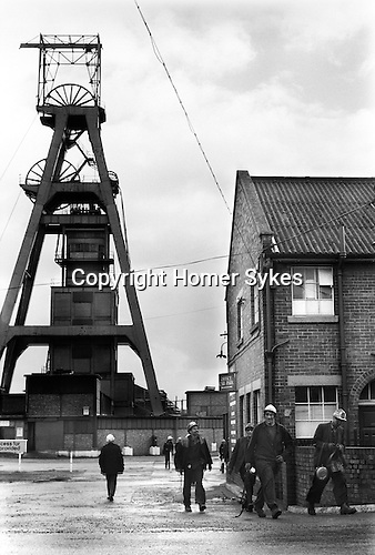 Snowdown, Kent. 1976<br /> The Snowdown Colliery pithead gear, miners some with their lamps still on make their way to the lamp room where they dropped off their 'pit checks' and recharged their lamps. There was a great feeling of camaraderie amongst the men. They were miners first and then their specific trade, never the other way around.