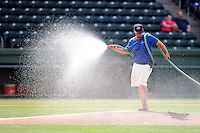 Head groundskeeper Greg Burgess of the Greenville Drive waters down the infield before a game against the Lexington Legends on Sunday, April 27, 2014, at Fluor Field at the West End in Greenville, South Carolina. Greenville won, 21-6. (Tom Priddy/Four Seam Images)