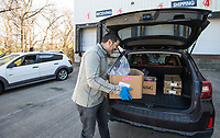 Chris Thompson, owner of Kimball and Thompson Produce, loads an order into a customer's vehicle Saturday, March 21, 2020, at the business in Lowell. The business supplies fresh produce to the food service industry, including public schools, restaurants and hotels. With many of their usual clients closed due to the covid-19 pandemic, Thompson says they are adapting to get their inventory directly to consumers who need it at wholesale prices. Thompson says he is also reaching out to the Northwest Arkansas Food Bank to make sure nothing goes to waste. <br /> <br /> The business began selling to the public Friday morning, and many shelves were already bare Saturday. Thompson says they will be working to keep their inventory updated as they navigate the temporary change to their business model. <br /> <br /> Staff and family members are pitching in to help fill orders curbside while minimizing personal contact and practicing strict sanitizing measures. Customers are asked to place orders ahead of time by calling 479-872-0200 or emailing orders@ktproduce.com. Pickup times are Monday through Saturday from 9 a.m. to 4 p.m., and Sunday from 11 a.m. to 2 p.m. at 305 S. Lincoln St. in Lowell. <br /> <br /> Check out nwaonline.com/200322Daily/ for today's photo gallery.<br /> (NWA Democrat-Gazette/Ben Goff)