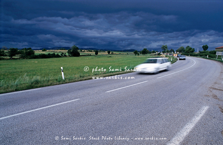 Cars driving under a stormy sky on the rural roads of Auvergne, France.