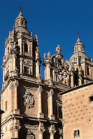 "Low angle view of Clerecia Church,  Salamanca, Spain, pictured on December 18, 2010 at midday with the Casa de las Conchas in the foreground. The Baroque style Clerecia Church, originally the Royal College of the Company of Jesus, was commissioned in the 17th century, from architect Juan Gomez de Mora, by Queen Margarita of Austria, wife of Philip III of Spain. It comprises two sections: the Jesuit school and church, with its three-storey Baroque cloister, and private living quarters for the monks and now houses the Salamanca Pontificia University. Salamanca, an important Spanish University city, is known as La Ciudad Dorada (""The golden city"") because of the unique golden colour of its Renaissance sandstone buildings. Founded in 1218 its University is still one of the most important in Spain. Around it the Old Town is a UNESCO World Heritage Site. Picture by Manuel Cohen"