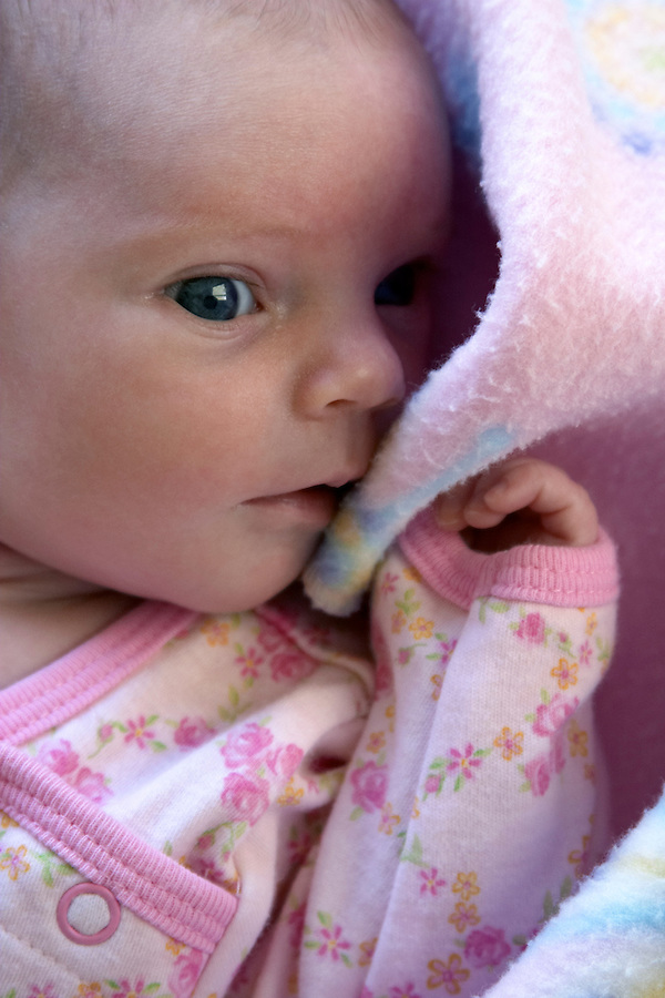 Infant girl being shy in pink blanket