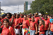 Flamboyan mas band pass by the landmark Trellick Tower on Children's Day at Notting Hill Carnival