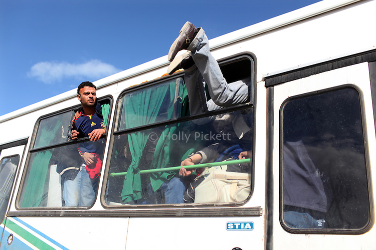 A man pulled himself into the window of a bus at the Tunisia-Libya border near Ben Guerdane, Tunisia, Friday, Feb. 26, 2011. Thousands of foreign workers continued their exodus across the border into Tunisia, fleeing violence sparked by an uprising against Col Muammar Qaddafi. The refugees, primarily Egyptians, had to wait at the border or at an improvised camp nearby until a bus could take them to the airport in Tunis.