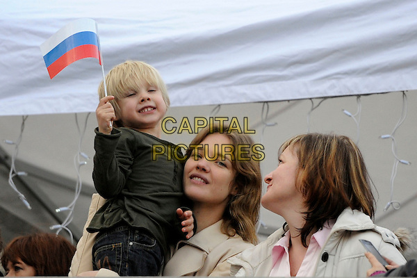 Viktor & Natalia Vodianova  .The Russian Maslenitsa in Trafalgar Square, London, England..February 26th, 2012.The Russian Maslenitsa in Trafalgar Square, London, England..February 26th, 2012 .half length carrying holding kid child mother mom mum son family beige leather flag waving .CAP/IA.©Ian Allis/Capital Pictures.