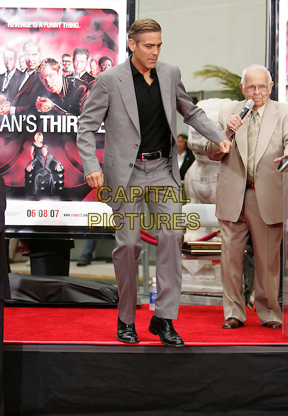 GEORGE CLOONEY.The Warner Brothers Pictures Hand & Foot Print Ceremony for The Cast of Ocean's Thirteen held at The Grauman's Chinese Theatre in Hollywood, California, USA..June 5th, 2007                     .full length grey gray suit jumping gesture funny.CAP/DVS.©Debbie VanStory/Capital Pictures