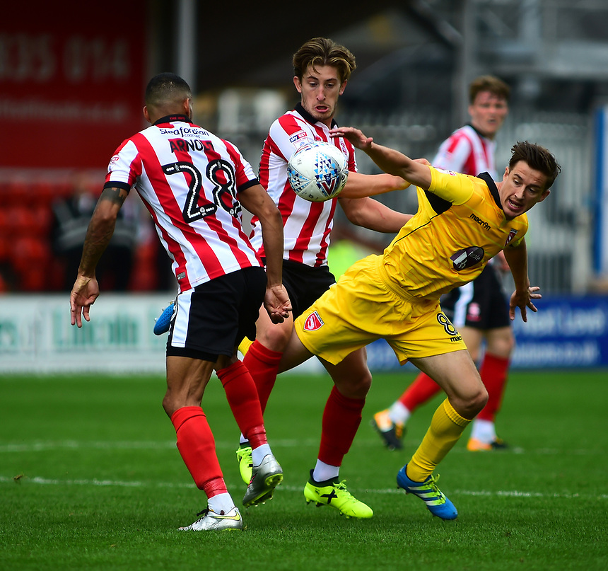 Lincoln City's Alex Woodyard and Nathan Arnold vies for possession with Morecambe's Andrew Fleming<br /> <br /> Photographer Andrew Vaughan/CameraSport<br /> <br /> The EFL Sky Bet League Two - Lincoln City v Morecambe - Saturday August 12th 2017 - Sincil Bank - Lincoln<br /> <br /> World Copyright &copy; 2017 CameraSport. All rights reserved. 43 Linden Ave. Countesthorpe. Leicester. England. LE8 5PG - Tel: +44 (0) 116 277 4147 - admin@camerasport.com - www.camerasport.com
