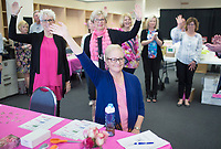NWA Democrat-Gazette/CHARLIE KAIJO Cancer survivors raise their hands, Thursday, April 12, 2018 at  the Race for the Cure, Koman Ozark Affiliate, office in Rogers.<br />