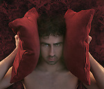 A naked young man holding red cushions over his ears