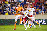 Bobby Boswell (32) of the Houston Dynamo and Joel Lindpere (20) of the New York Red Bulls battle for the ball during a Major League Soccer (MLS) match at Red Bull Arena in Harrison, NJ, on August 10, 2012.