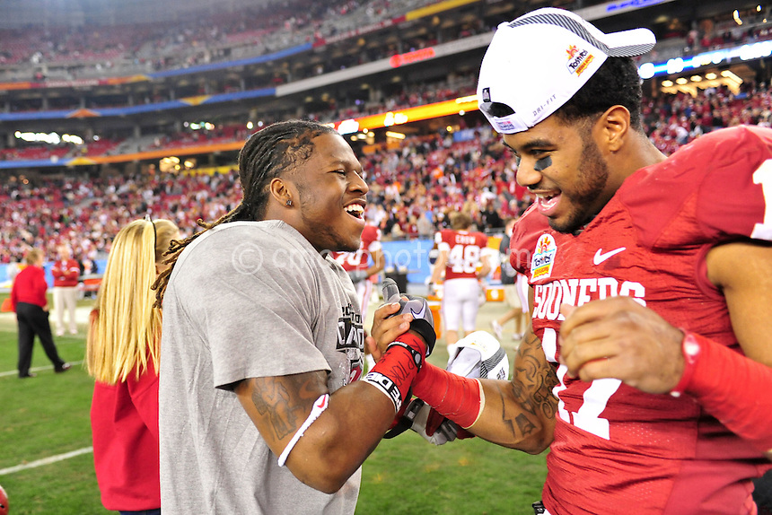 Jan 1, 2011; Glendale, AZ, USA; Oklahoma Sooners defensive back Marcus Trice (13) and running back Mossis Madu (17) celebrate after a 48-20 victory over the Connecticut Huskies in the 2011 Fiesta Bowl at University of Phoenix Stadium.  The Sooners won the game 48-20.