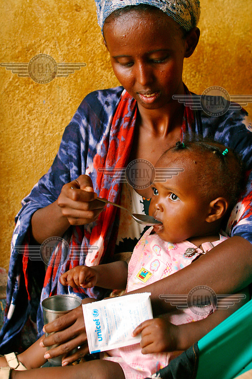 A woman giving oral rehydration salts to her child.