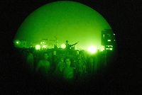 "Baghdad, Iraq, June 6, 2003.US Army soldiers on night patrol in Thawra (ex-Saddam City), the most dangerous area of Baghdad. The ""night vision"" googles reveal a dense crowd surrounding the Hummvees and...a ""Batman"" T-shirt!."