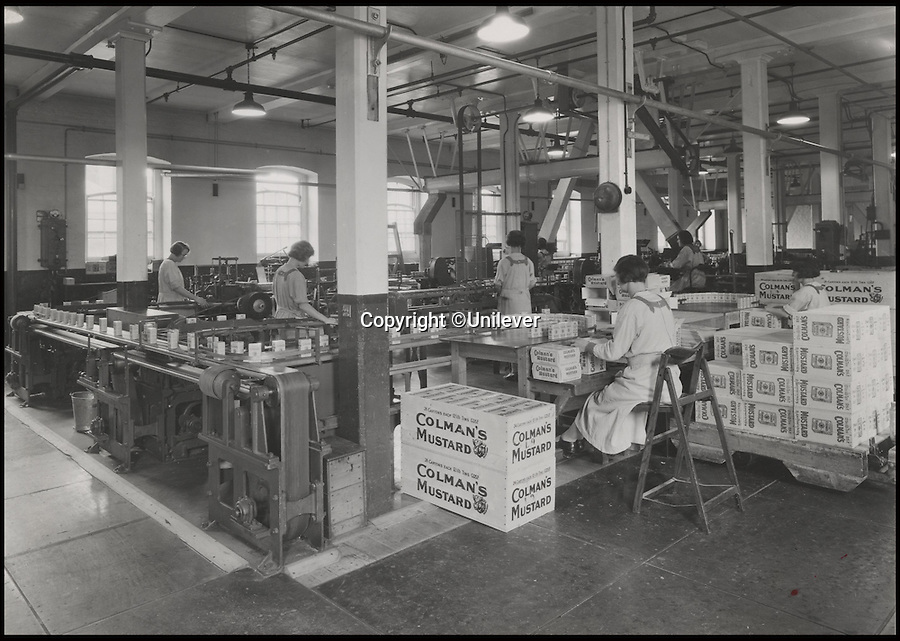 BNPS.co.uk (01202 558833)<br /> Pic: Unilever/BNPS<br /> <br /> Packing mustard in the 1930's.<br /> <br /> A staple of the British kitchen is celebrating its anniversary this year as Colman's Mustard turns 200.<br /> <br /> Archivist's research reveals the 200 year history of Colmans mustard.<br /> <br /> Founded in Norwich in 1814 by Jeremiah Colman, the super hot condiment made from Norfolk mustard seeds soon become a family favourite at dinner tables throughout the Empire, with even Capt Scott taking a case on his ill fated Terra Nova expedition to the south pole.<br /> <br /> So vital was the powdered sauce that it escaped wartime rationing to keep the home fires burning during the dark days of WW2. <br /> <br /> Despite being founded a year before Napoleon met his Waterloo, the world famous brand still produces 3000 tons of the fiery favourite every year exporting to all parts of the globe.