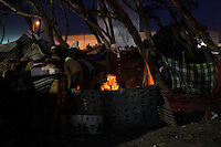 Refugees gather around a fire. Tens of thousands of people, mainly migrant workers, fled unrest in Libya and crossed the border into Tunisia. Some slept in the open for several days before being processed.  At the same time forces loyal to Col. Gaddafi fought opposition forces in various parts of the country.