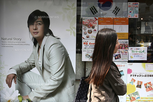 July 23, 2010 - Tokyo, Japan - A woman walks past a commercial poster featuring the South Korean actor Bae Yong-joon, near JR Shin-okubo station in Tokyo, Japan, on July 23, 2010. Japanese fans of South Korean actor and singer Park Yong-ha, who commits suicide on June 30th, visited a memorial altar set up at a Korean restaurant in Tokyo's Okubo district, where many Koreans live.
