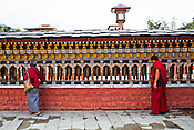 An old Bhutanese woman and a lama are seen turning the prayer wheels at the clock tower, the main square in Thimphu, Bhutan. Photo: Sanjit Das/Panos