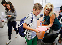 NWA Democrat-Gazette/DAVID GOTTSCHALK   Kenton Lambert (center), a freshman at Fayetteville High School, reviews his class schedule with his mom Kristen Speer (right) at the end of Algebra Class in Bartt Foster's classroom at the high school Monday, August 17, 2015. Freshman students picked up their class schedules today and attended a half day of school in preparation for the year. Parents were invited to attend and escort their children through the shorten class schedule.