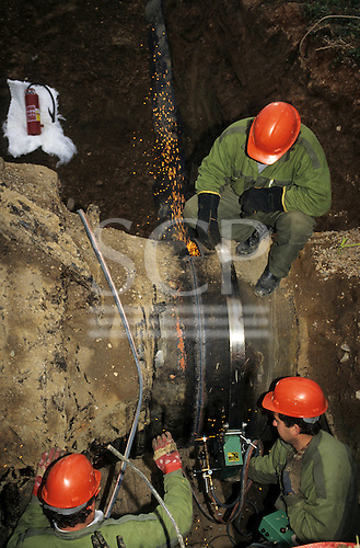 Slovakia: workers in green overalls and red hard hats cutting a pipeline using gas cutting equipment.