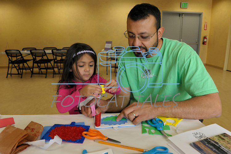 Gilbert Martinez, right, and his daughter Avani, 4, both of Sparks, create a framed wildflower during Nevada Wildflower Family Fun Day at the Nevada State Museum in Carson City Saturday April 11, 2015. Visitors to the museum were treated to loads of information, hands-on experiences and crafts.<br /> Photo by Lisa J. Tolda