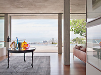 The contemporary home has a relaxed, peaceful quality with a seamless connection between indoor and outdoor living. Concrete is used in the ceilings and walnut wood floors add warmth. The floor to ceiling picture windows makes the most of the spectacular view. A group of glass vases on a round table make a colourful display.