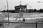 People walking past a section of the Berlin Wall at the Brandenburg Gate, seen from the western side of the divide. The Berlin Wall was a barrier constructed by the German Democratic Republic (GDR, East Germany) starting on 13 August 1961, that completely cut off West Berlin from surrounding East Germany and from East Berlin. The Wall was opened on 9. November 1989 allowing free movement of people from east to west.