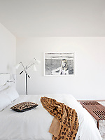 The white bedroom is simply furnished with a double bed and wooden bench seat.