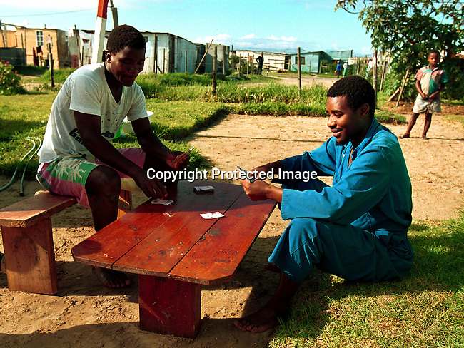 ditown00139 Township.  Daily life in Khayelitsha, a poor township outside cape town, South Africa. Hundres of thousands of people live in shacks in these areas, about 25 kilometers (15 miles) from Central Cape Town. Two men playing a card game on a lawn, shacks. Leisure. Wooden table and benches.©Per-Anders Pettersson/iAfrika Photos