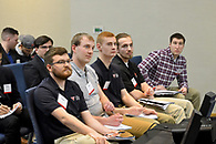 Fraternity students listening attentively to a workshop presentation on life skills.