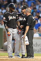 Miami Marlins shortstop Jose Reyes #7 is checked on by manager Ozzie Guillen #13 and team trainer after fouling a pitch off his leg during a game against the Chicago Cubs at Wrigley Field on July 17, 2012 in Chicago, Illinois. The Marlins defeated the Cubs 9-5. (Tony Farlow/Four Seam Images).
