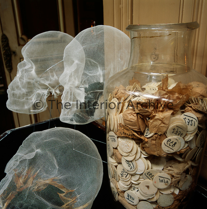 An eerie contrast between numbered discs and brown paper in an old glass jar and three dimensional skulls made of mesh.