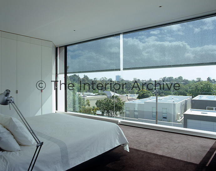The picture window in the simple master bedroom has a view of Melbourne