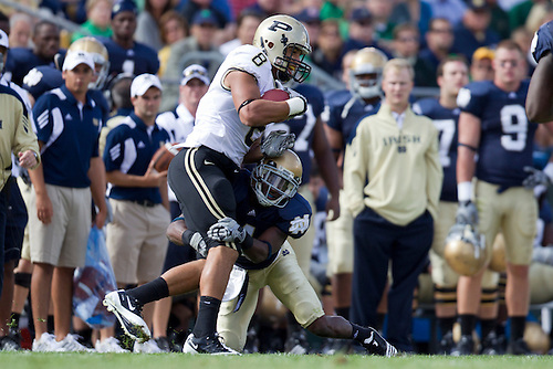 Notre Dame cornerback Gary Gray (#4) makes tackle on Purdue wide receiver Keith Smith (#8) in game action during NCAA football game between the Notre Dame Fighting Irish and the Purdue Boilermakers.  Notre Dame defeated Purdue 23-12 in game at Notre Dame Stadium in South Bend, Indiana.