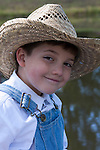 An old fashioned young farmer boy smiling next to a pond