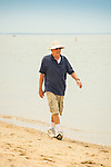 Senior man walking along shore.