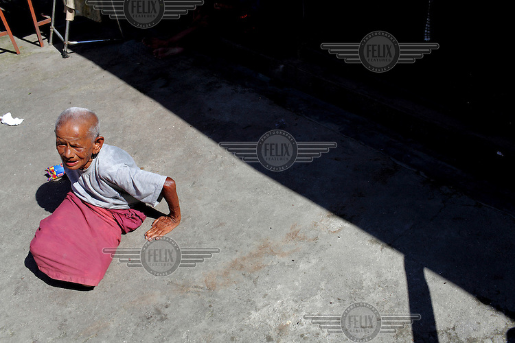 An elderly man sits on a street passing his last days in misery. With provisions scarce, there is not enough food.