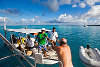 Man receiving bread delivery in morning on yacht from Tahitians in skiff
