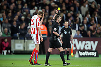 Peter Crouch of Stoke City is booked after celebrating his goal with jumping into the crowd during West Ham United vs Stoke City, Premier League Football at The London Stadium on 16th April 2018